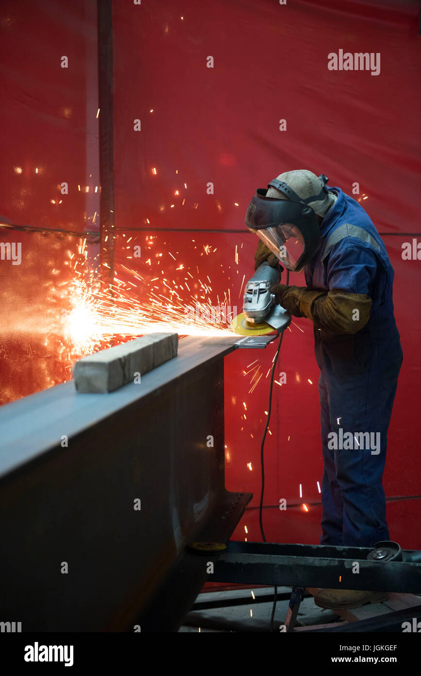 Workers at a steel fabrication facility welding and grinding steel in Caldicot, Wales, UK. - Stock Image
