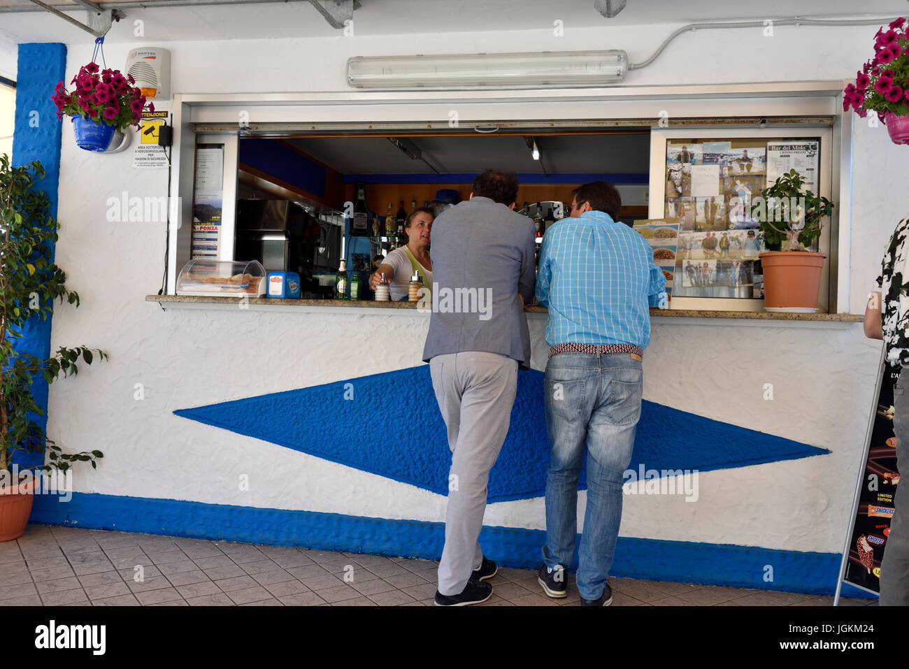 The backs of two men looking in the serving window of dinner - Stock Image