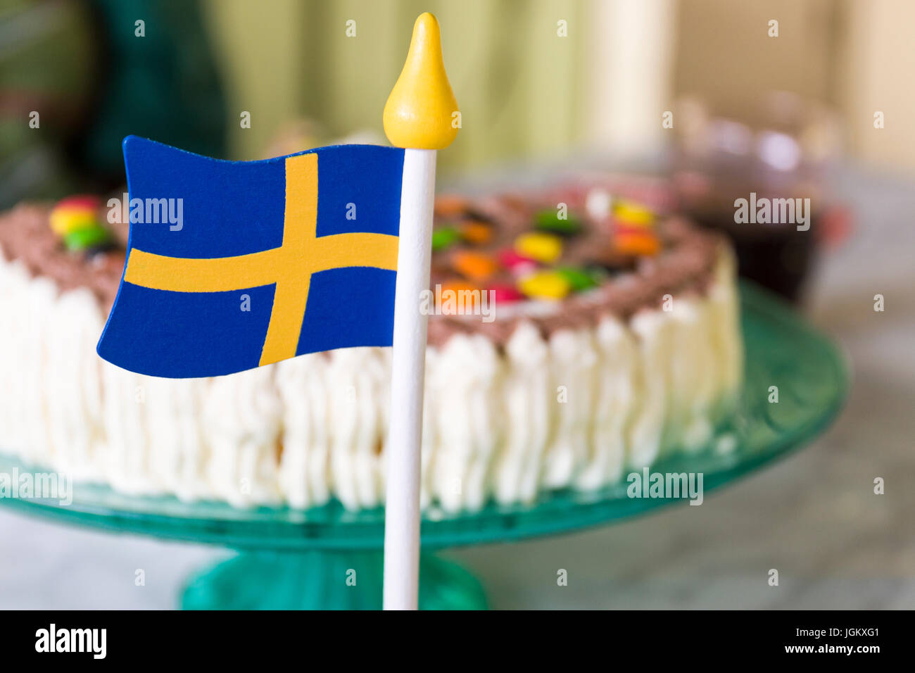 Small wooden swedish flag on table in front of beautifully decorated cake during celebration  Model Release: No. - Stock Image