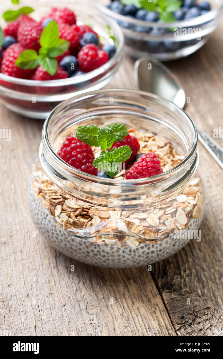 Healthy dietary breakfast. Chia pudding with muesli, raspberries, blueberries in a glass bowl, fresh berries on - Stock Image