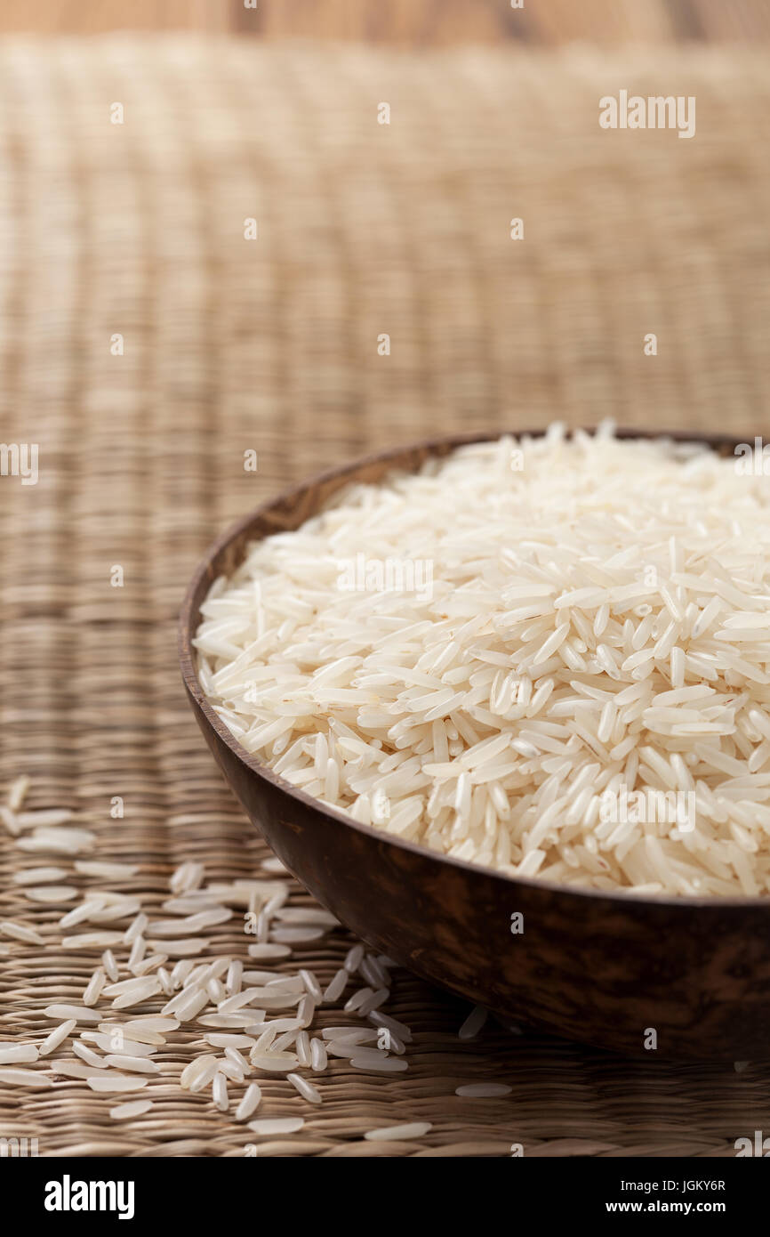 Basmati rice in wooden bowl on straw background - Stock Image