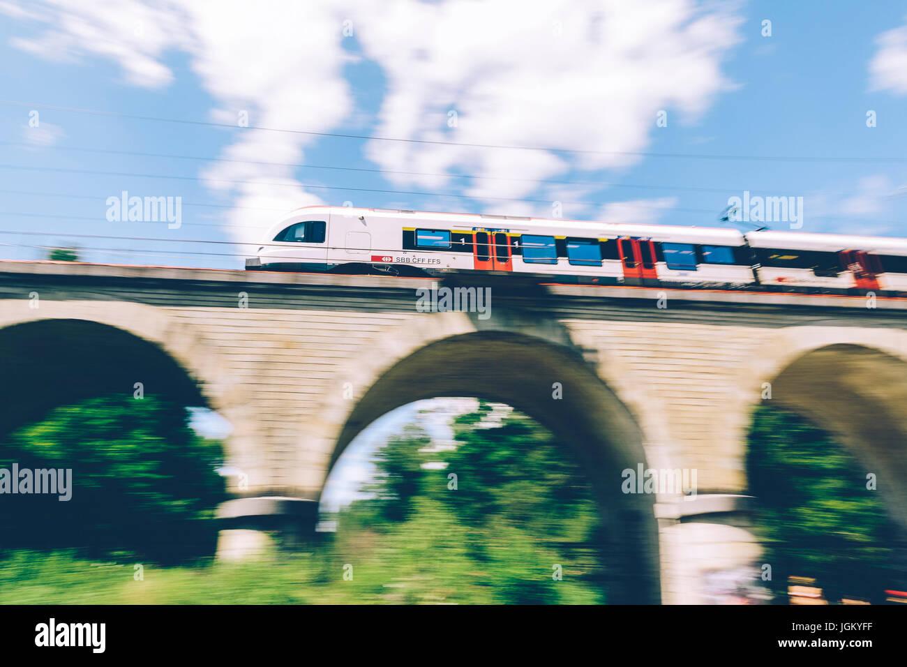 Geneva, Switzerland - June 25, 2017: Swiss regional train passing over a bridge in the Geneva Canton region, with motion blur. Stock Photo