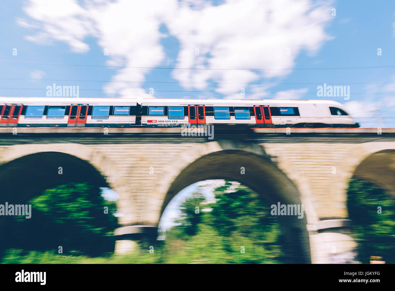 Geneva, Switzerland - June 25, 2017: Swiss regional train passing over a bridge in the Geneva Canton region, with - Stock Image