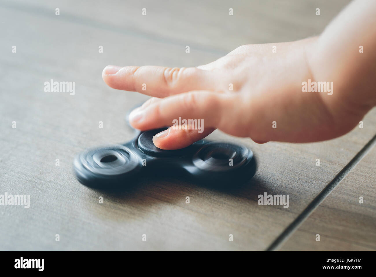 Closeup of a child's hand playing with a fidget spinner - Stock Image