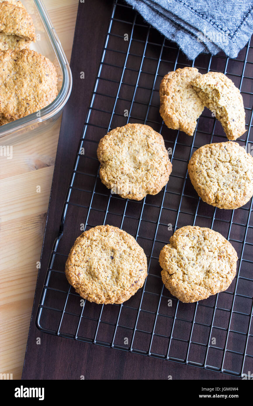 Gluten free homemade oatmeal cookies and napkin on cooling rack. Vertical. Selective focus - Stock Image