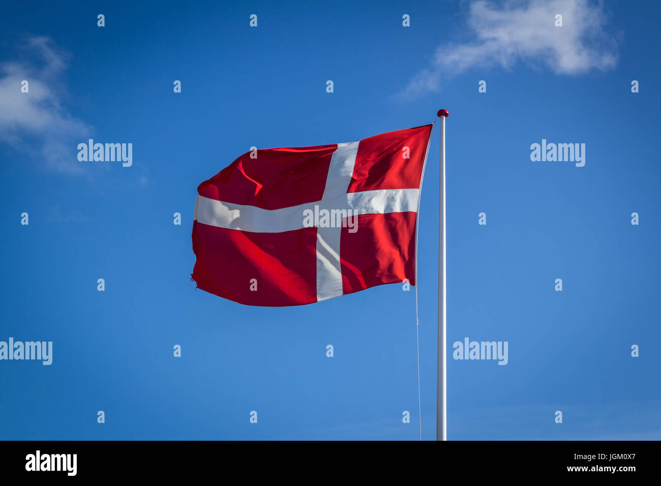 Danish flag in sunshine against blue sky with clouds, horizontal - Stock Image