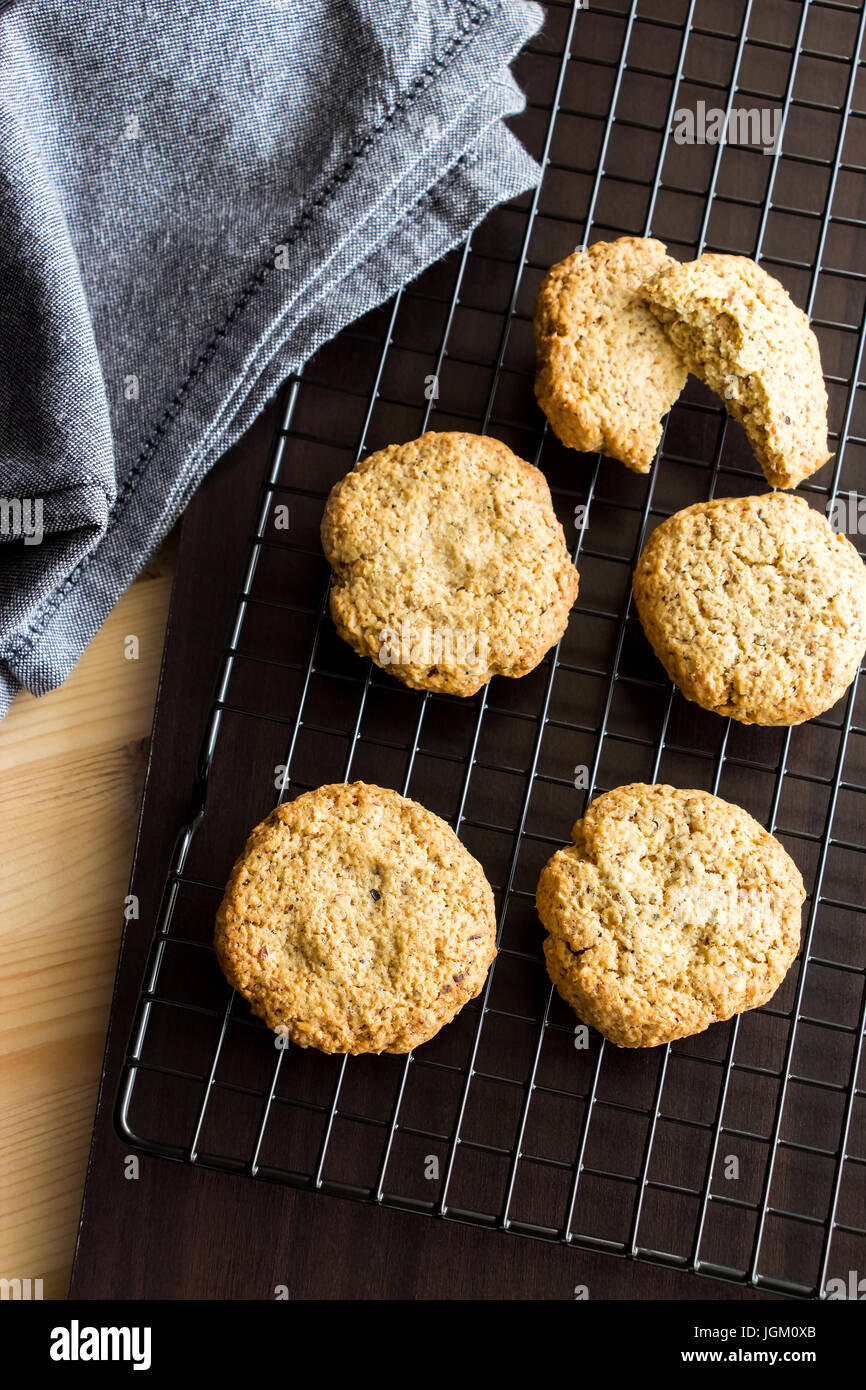 Gluten free homemade oatmeal cookies and napkin on cooling rack. Vertical. Selective focus. Toned photo - Stock Image