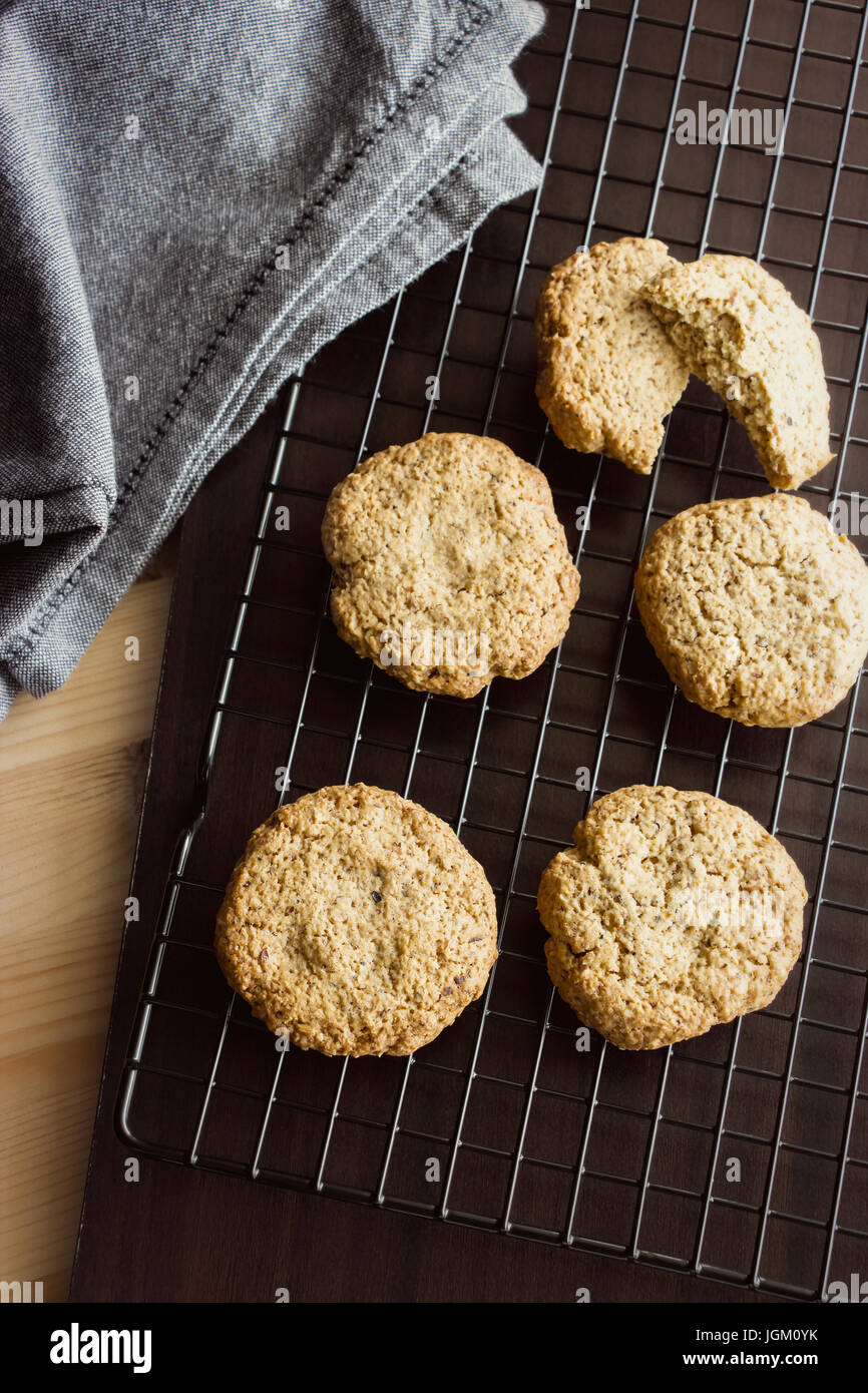 Gluten free homemade oatmeal cookies and napkin on cooling rack. Vertical. Selective focus. Light toned - Stock Image