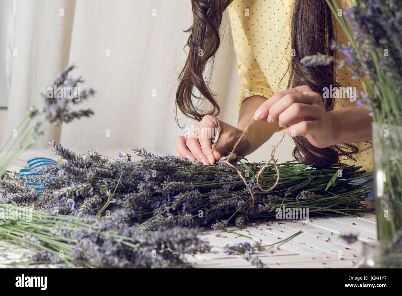 Florist at work: woman creating bouquet of natural lavender flowers, tying the flowers with a rope in te wooden - Stock Image