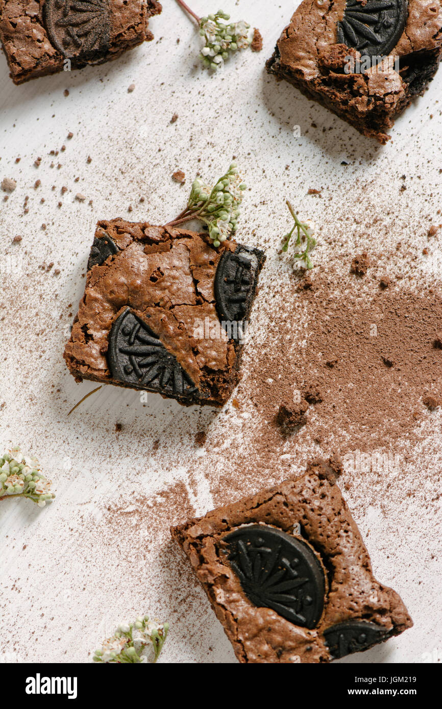 Chocolate brownies, with black biscuit stuffed with cream, stacked from above Stock Photo