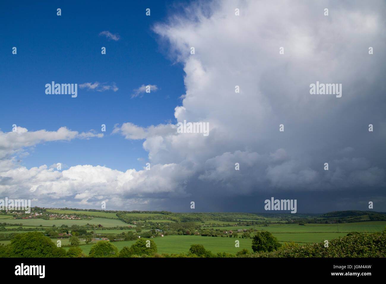 A large storm cloud with falling rain above the Chiltern Hills in Buckinghamshire. - Stock Image