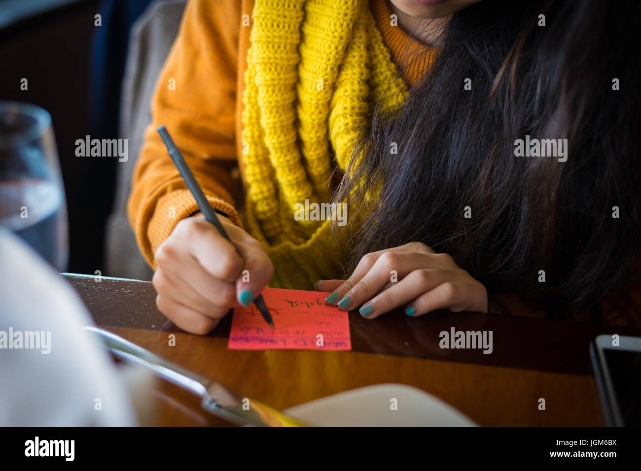 Girl writing a note to post onto the Space Needle - Stock Image
