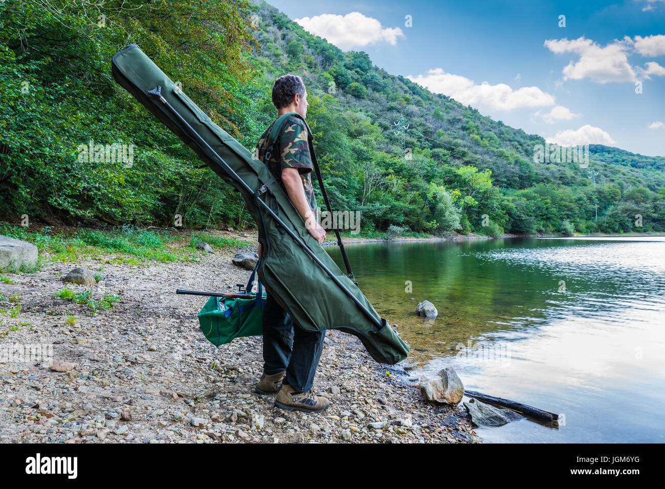 Fishing adventures, carp fishing. Fisherman on a lake shore with camouflage fishing gear, green bag and mimetic - Stock Image