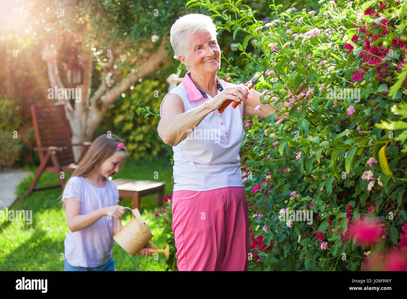 Family Gardening, Grandma With Grandchild Pruning And Watering.   Stock  Image