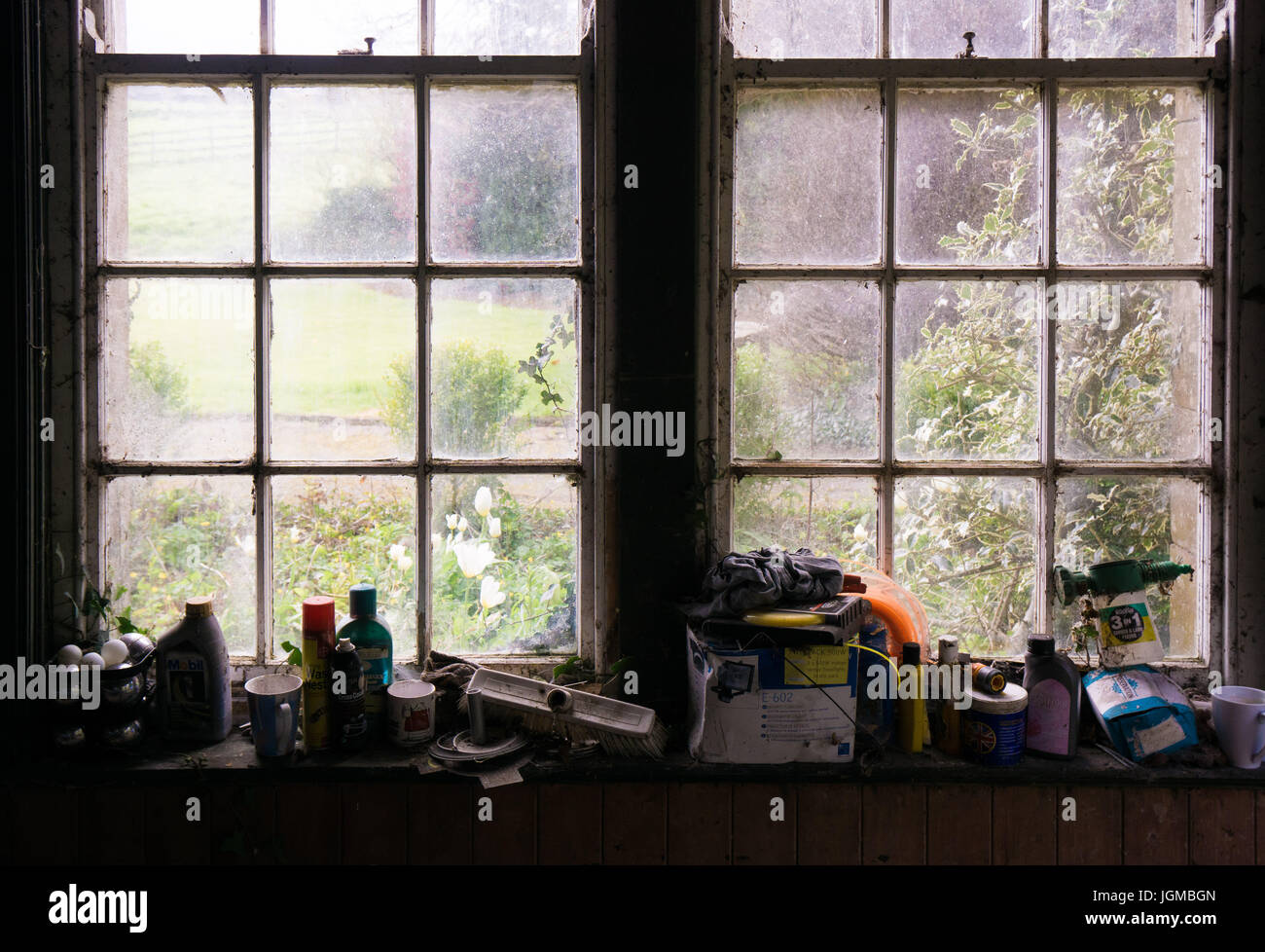 An old and dirty window with a feeling of neglect and melancholy - Stock Image