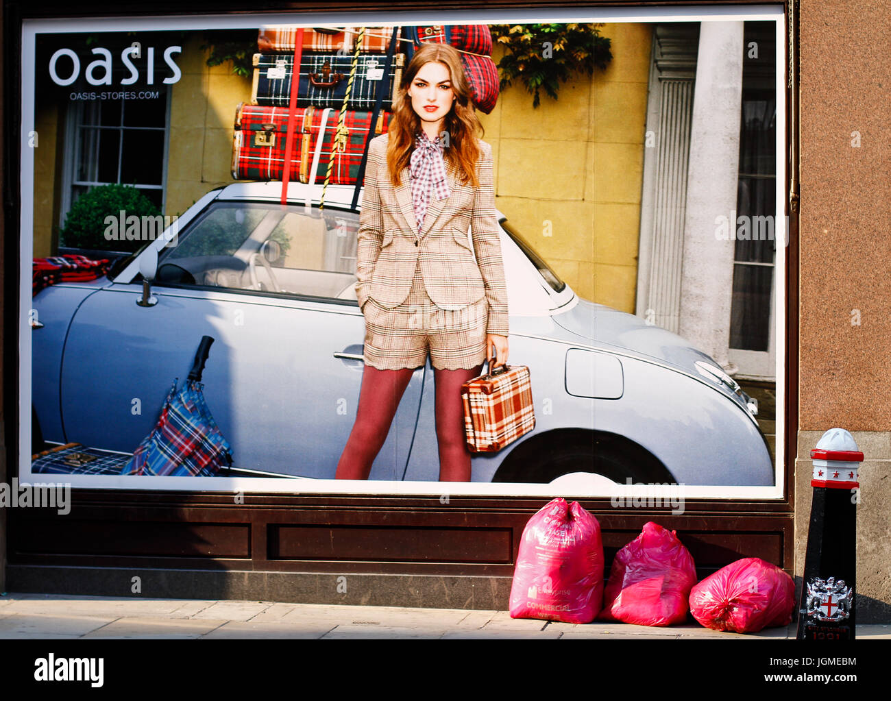 big advert on the wall with few rubbish bags placed under advertisement. Girl holding trendy bag. car packed with - Stock Image