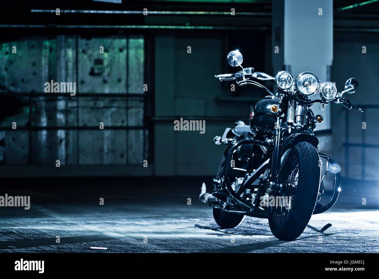 motorbike parked in the garage. Modified Harley Davidson Bobber parked in underground garage. Stock Photo