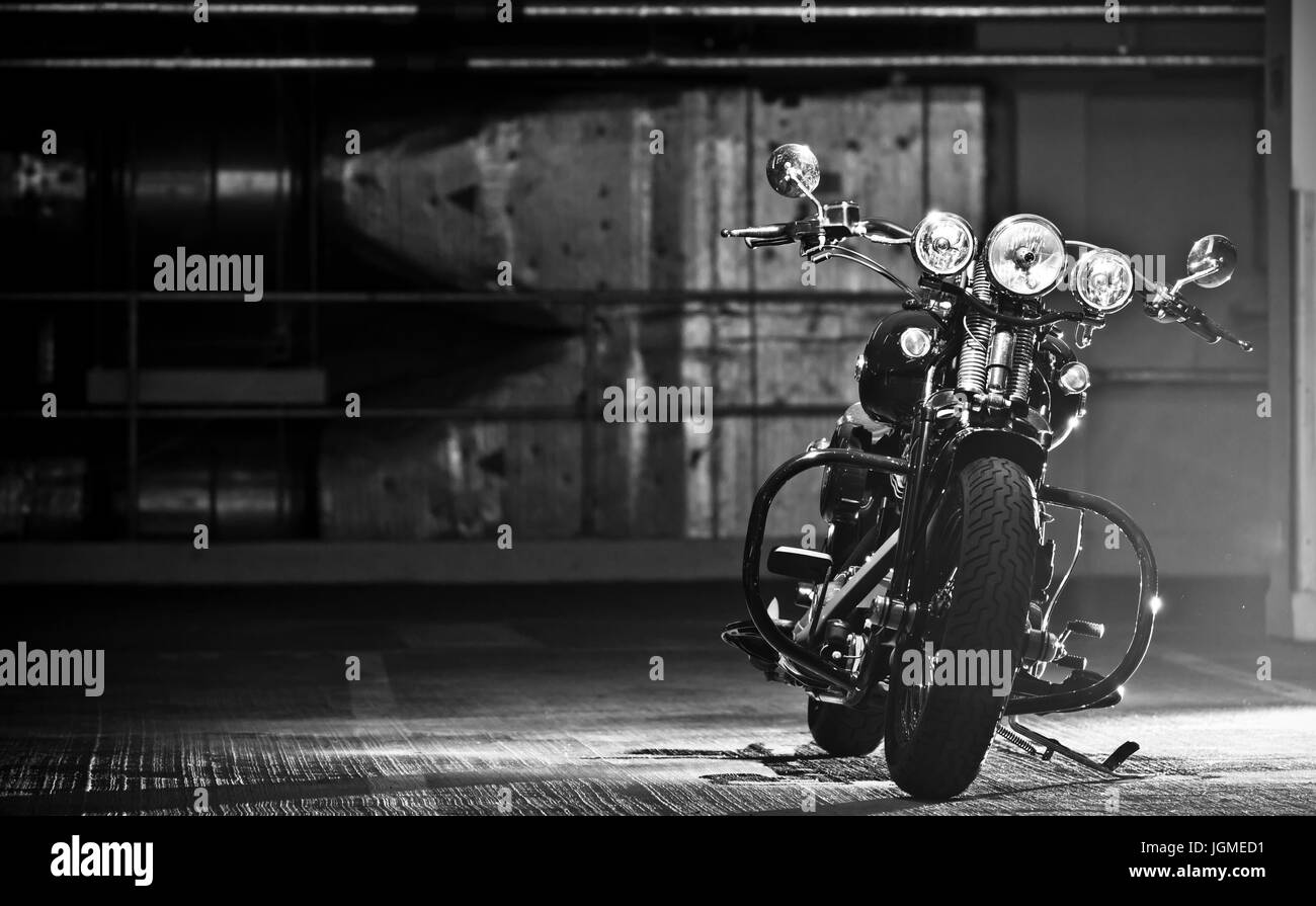 motorbike parked in the garage. Modified Harley Davidson Bobber parked in underground garage. - Stock Image