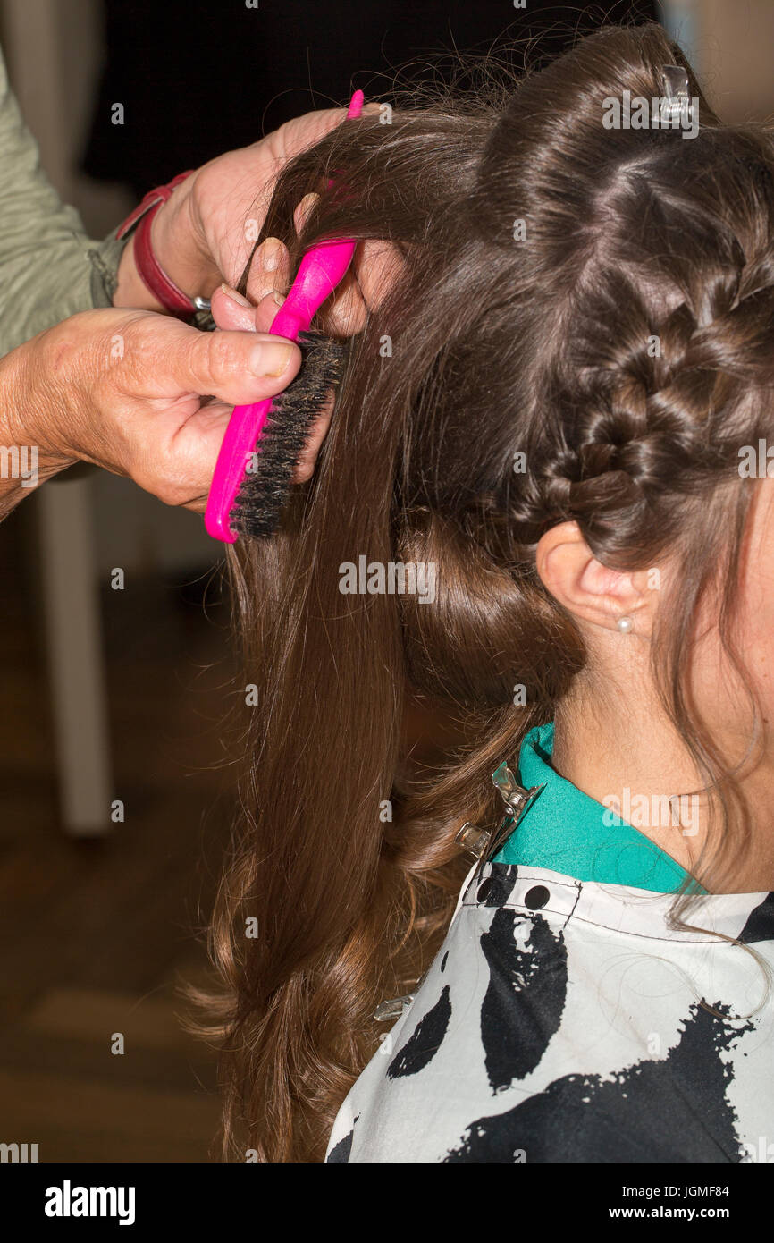 Hairdresser makes upper bun chignon wedding hairstyle close-up - Stock Image
