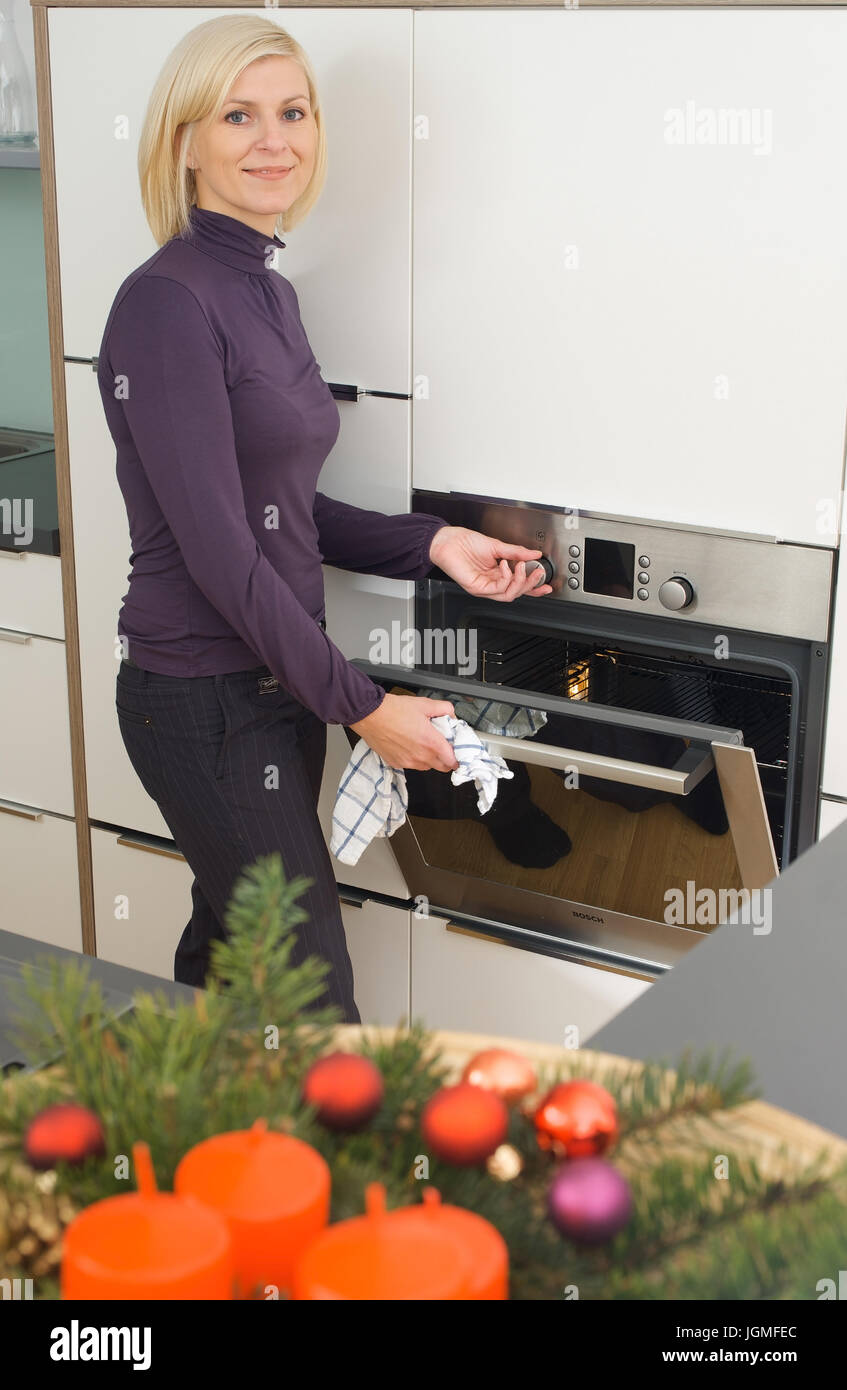 Housewife opens the oven - Housewife open the baking oven, Hausfrau öffnet den Backofen - Housewife open the baking Stock Photo