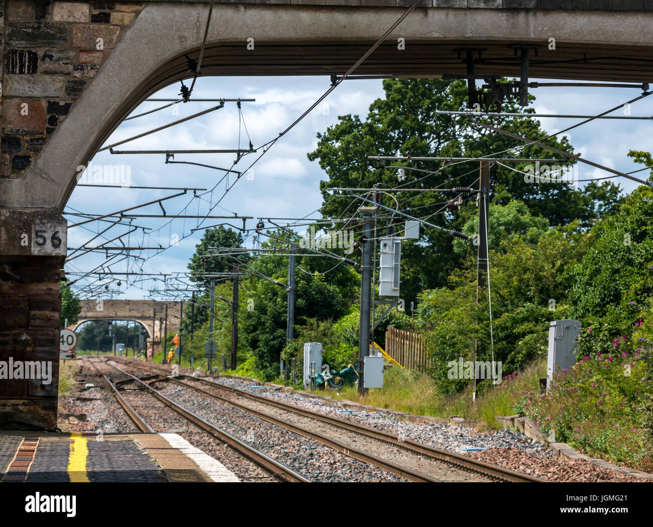 Looking through small stone bridge along railway train tracks, Drem station, East Lothian, Scotland, UK,with orange - Stock Image