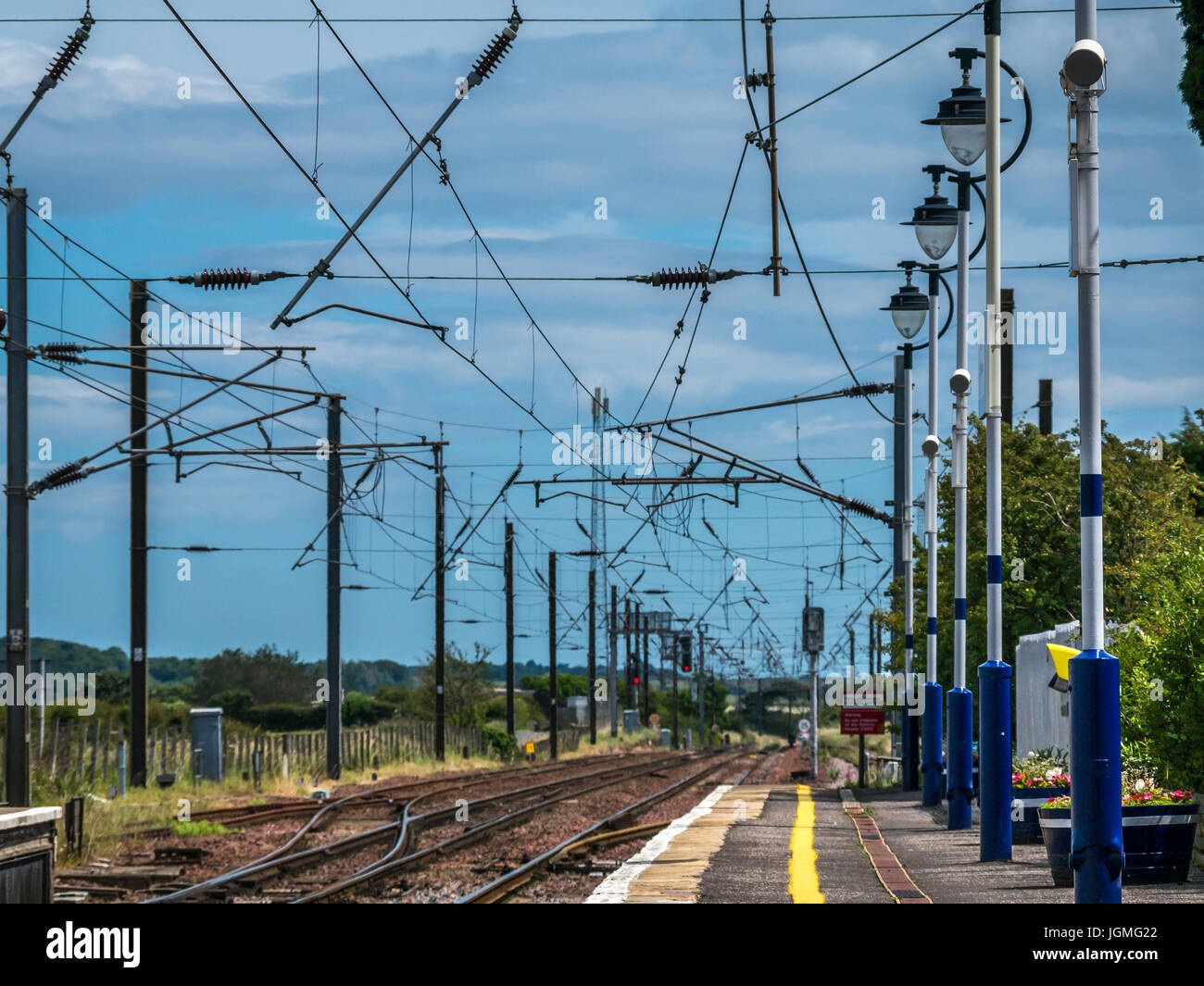 Drem train staton platform and view down railway tracks with overhead cables, East Lothian, Scotland, UK - Stock Image
