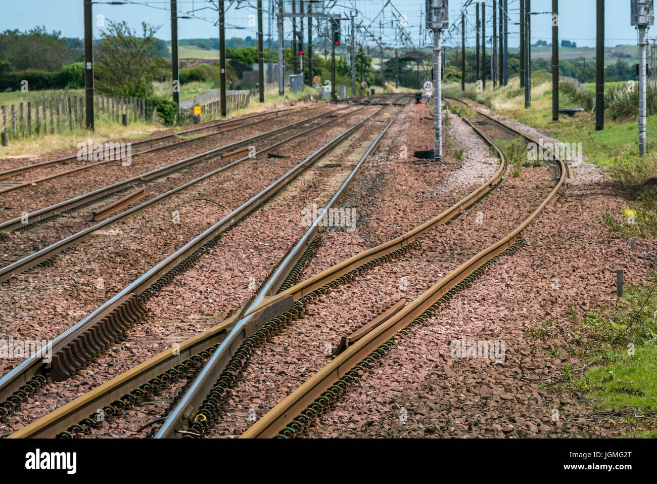 Parallel railway tracks with curved cutting, signals and overhead cables, Drem train station, East Lothian, Scotland, - Stock Image