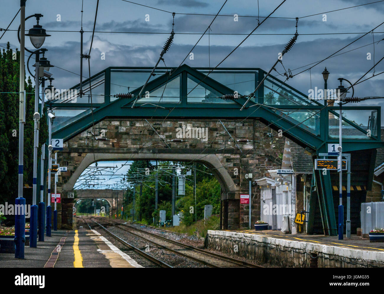 Looking through small stone bridge along railway train tracks, Drem train station, East Lothian, Scotland, UK - Stock Image