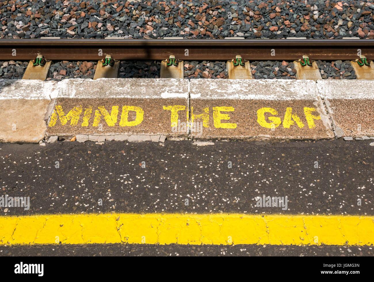 Mind the Gap warning painted in yellow letters on rural station platform, Drem, East Lothian, Scotland, UK - Stock Image