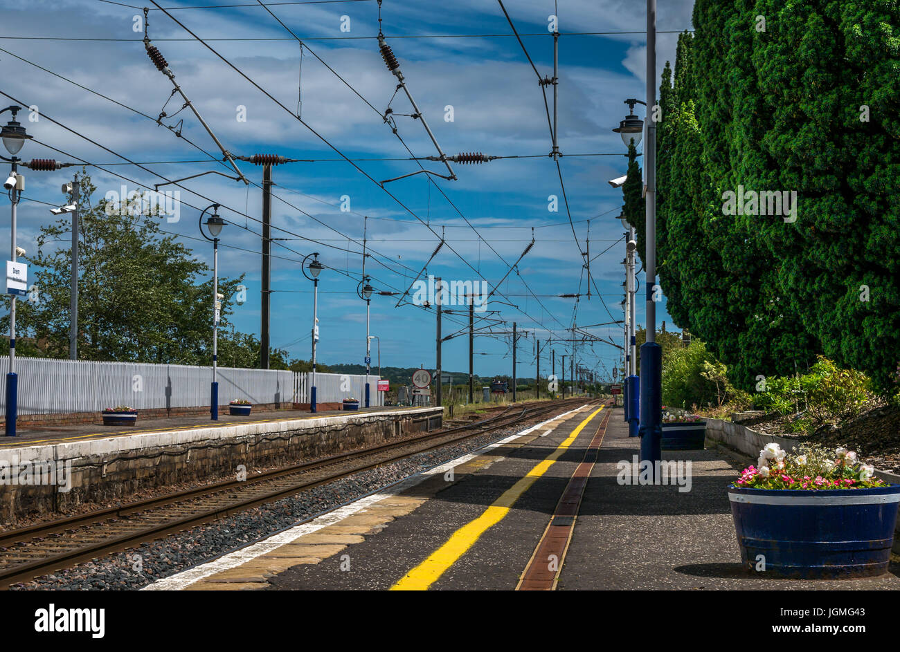 Train station platform at Drem, East Lothian, Scotland, UK, looking down railway tracks with overhead cables - Stock Image