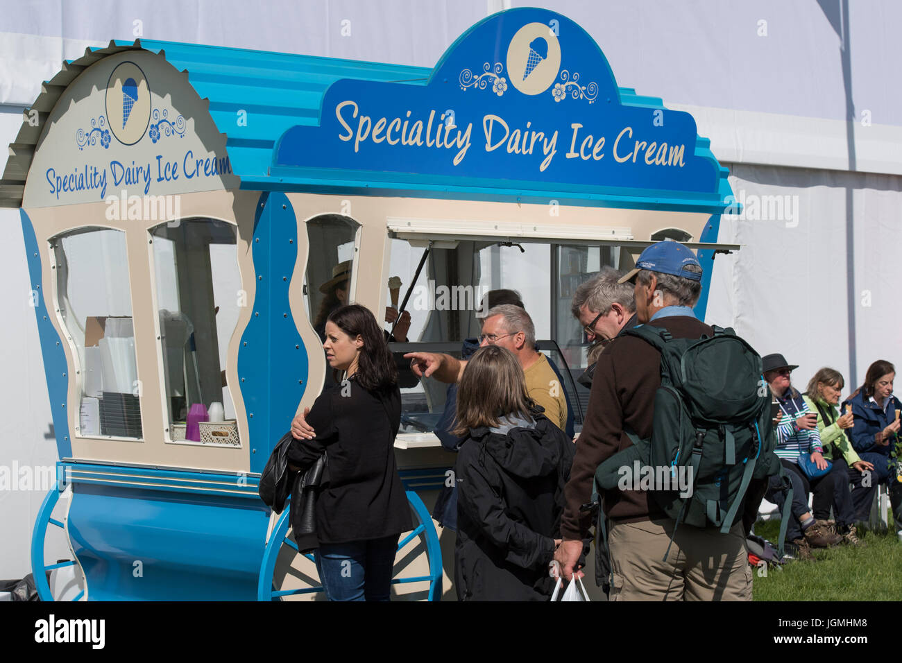 Quaint blue caravan selling ice cream to a queue of waiting people, parked at RHS Chatsworth Flower Show, Chatsworth - Stock Image