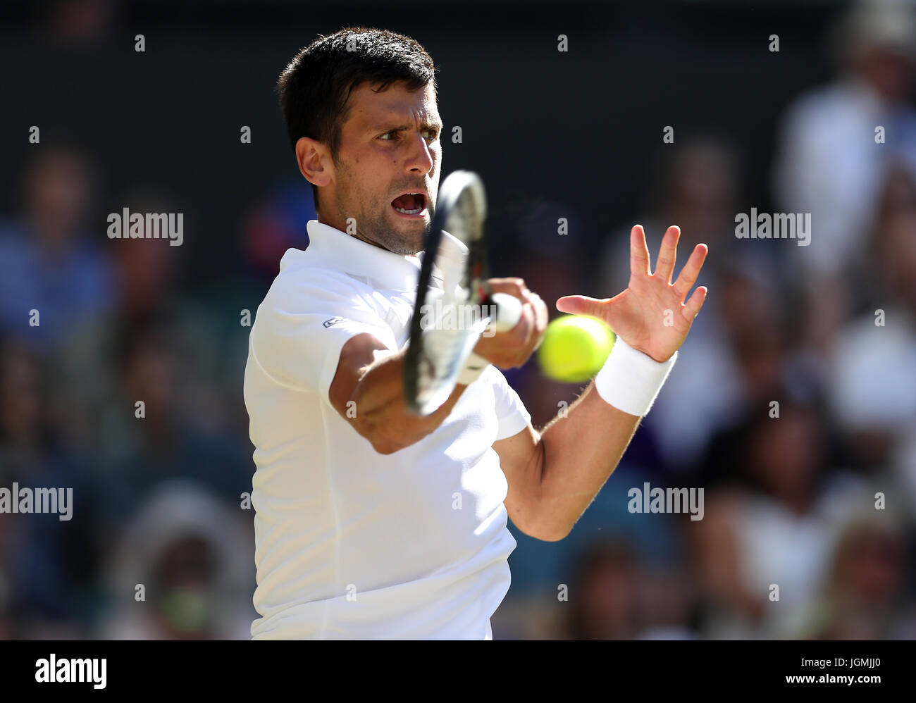 Novak Djokovic in action against Ernests Gulbis on day six of the Wimbledon Championships at The All England Lawn - Stock Image