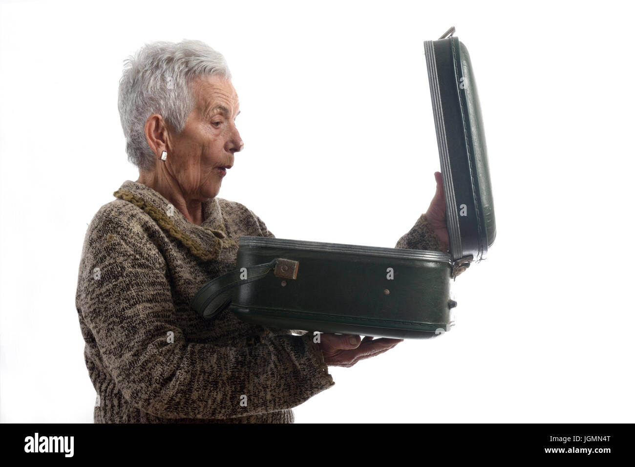 Surprised senior woman opening a vintage suitcase - Stock Image