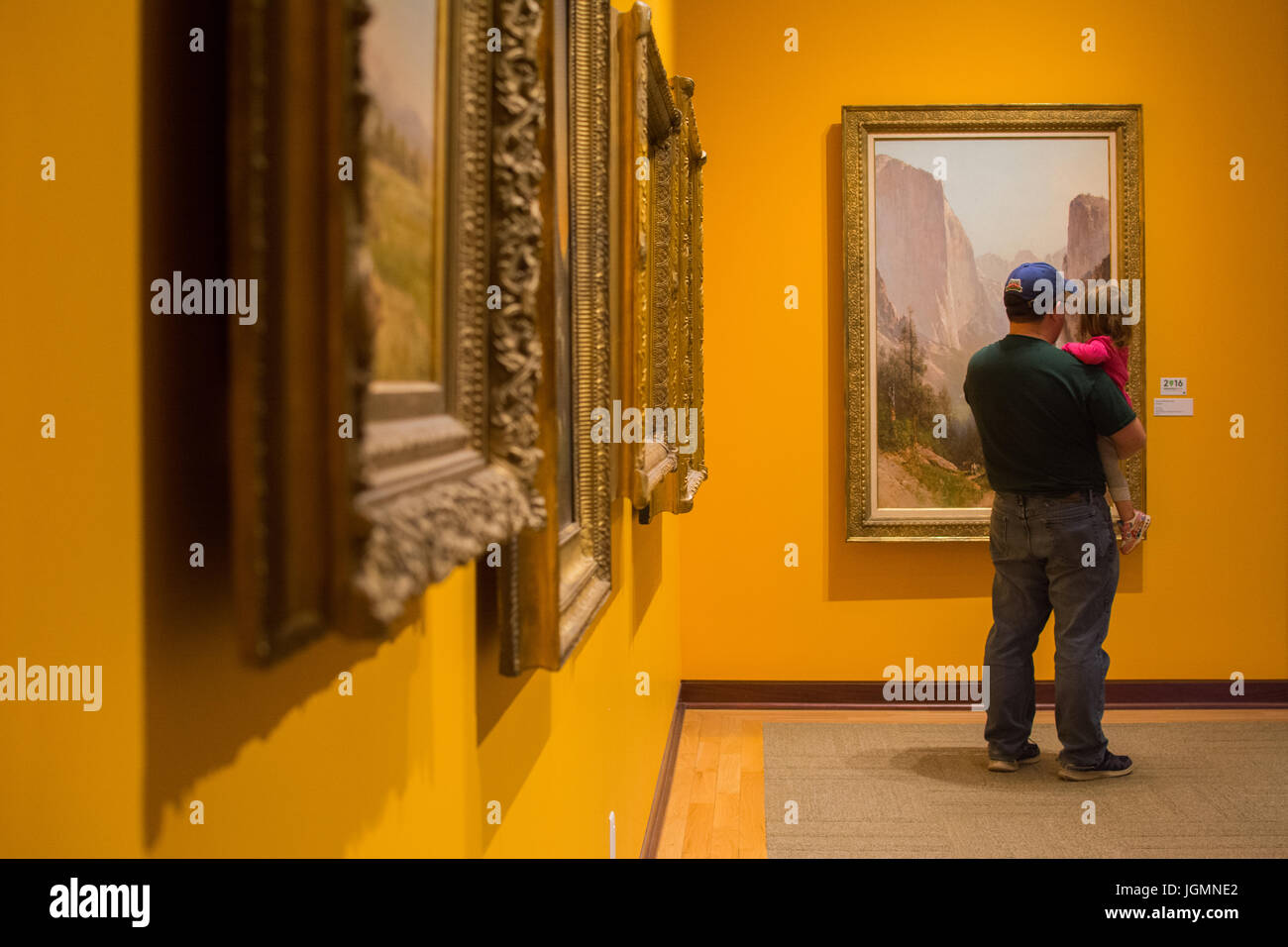 A man holds his toddler daughter and admires Western art at the Rockwell Museum of Western Art in Corning, N.Y. - Stock Image