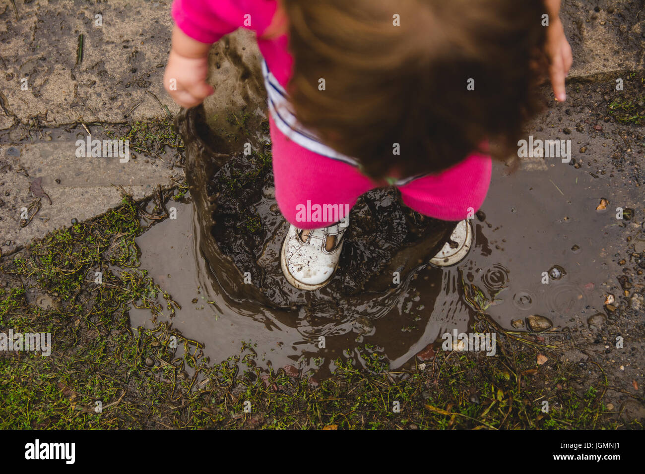 A 2-year old girl, looking down at ground and mud puddle, splashes in a mud puddle, making a mess of her clothes Stock Photo