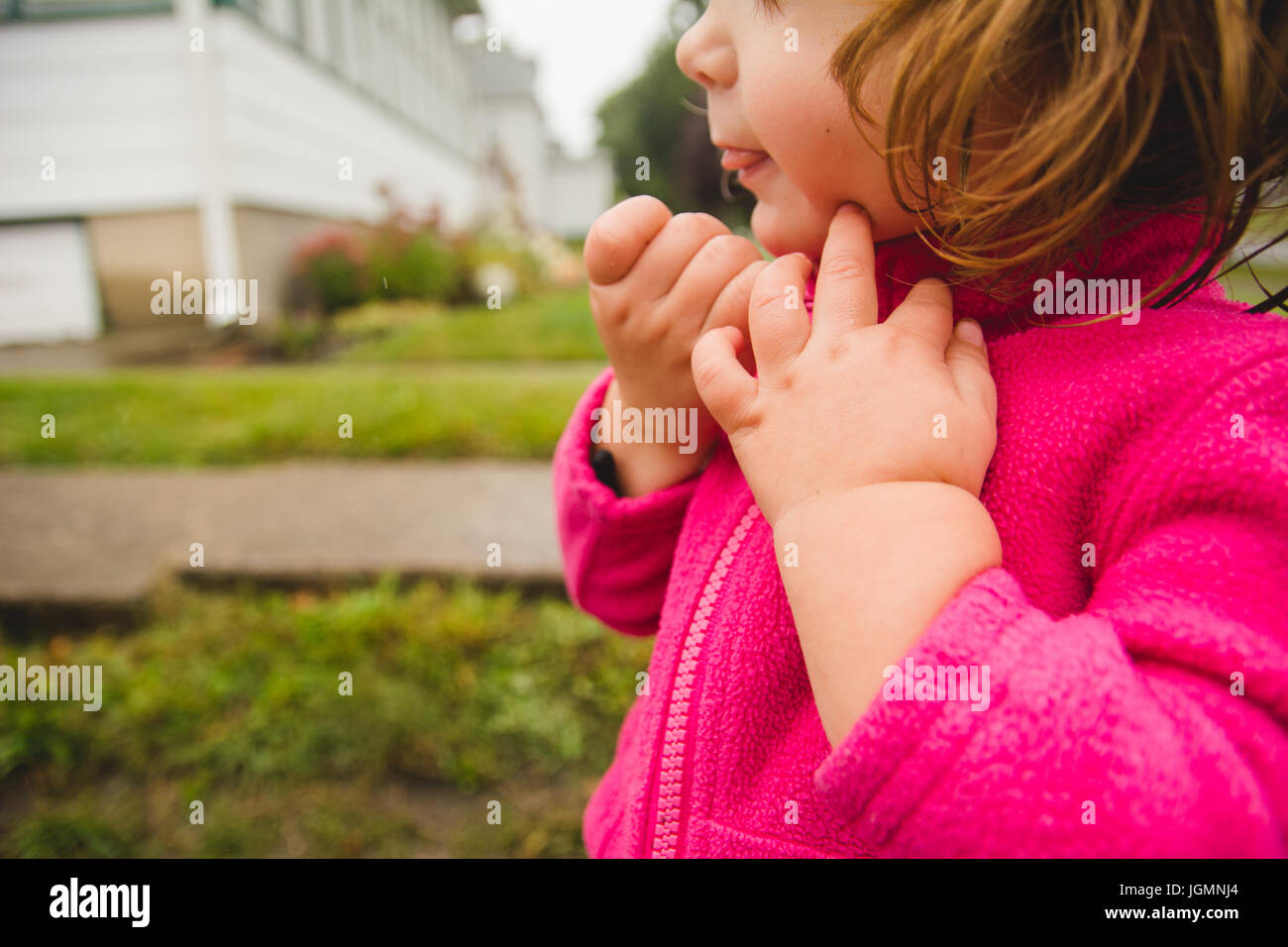 A toddler zipping her jacket hands only. Stock Photo