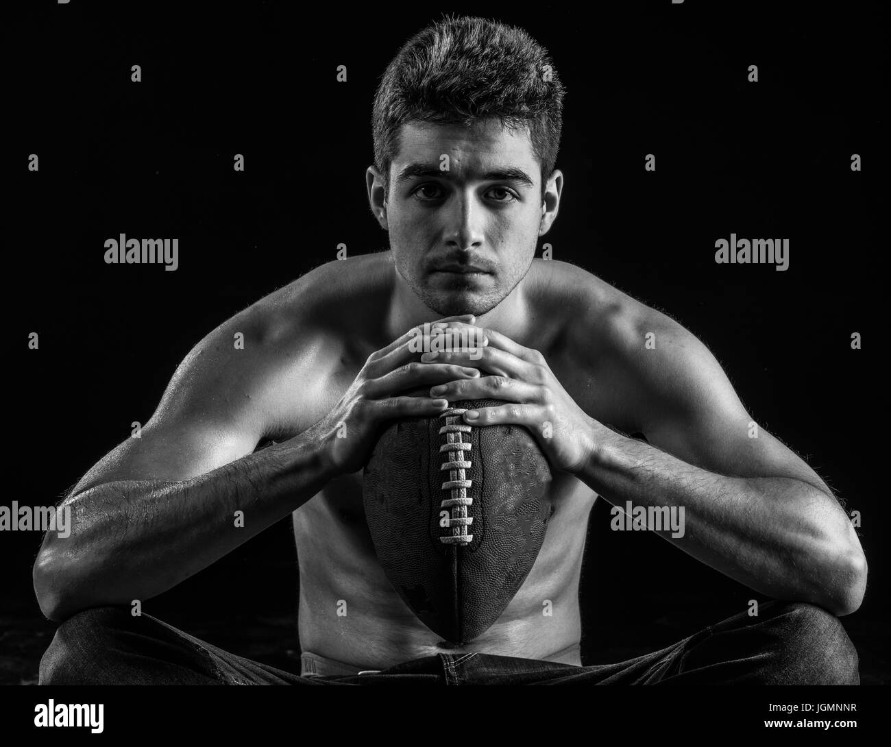 Football player portrait holding american football staring. - Stock Image