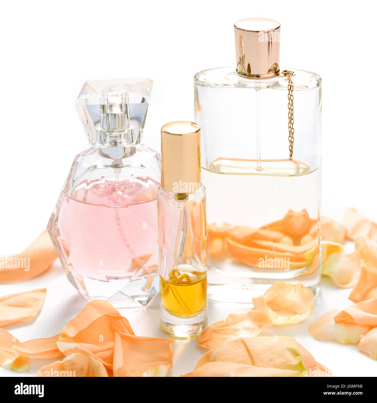 Perfume bottles with flower petals on light background. Perfumery, fragrance collection. Women accessories. - Stock Image
