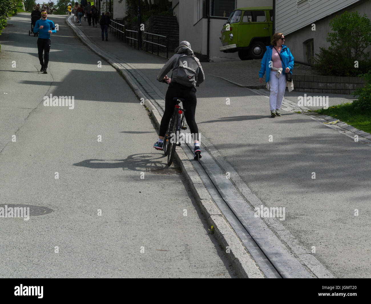 Young girl using the Trampe bicycle lift to ascend steep hill at Brubakken Nordheim Norway, runner descending hill - Stock Image