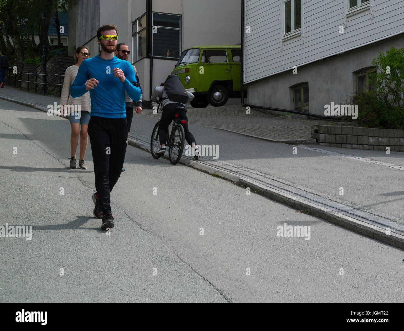 Young man running down steep hill at Brubakken a cyclist using Trampe bicycle lift to ascend the hill Trondheim - Stock Image
