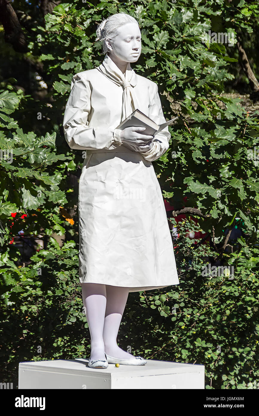 29.06.2017 ,Saint Petersburg , Russia .Mime painted in white color depicting a monument woman with a book ., summer - Stock Image