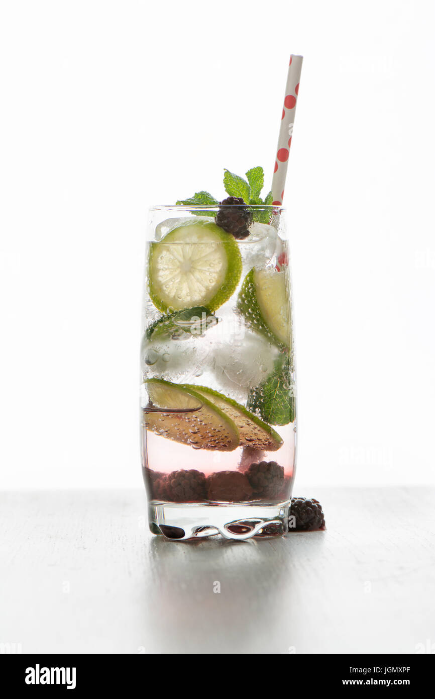Gin tonic cocktail with lime, ice and red fruit, white background - Stock Image