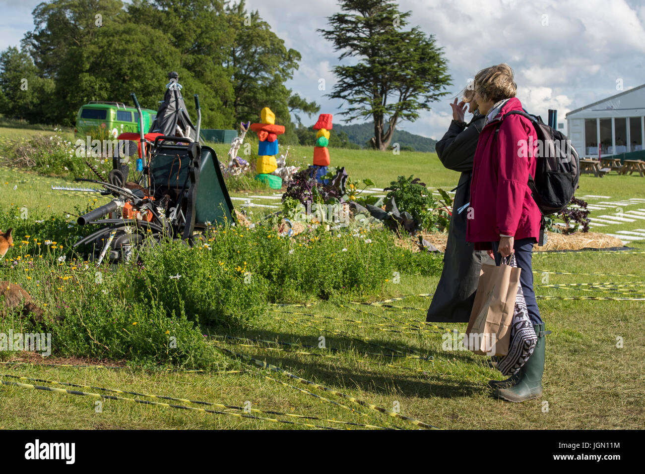 Two people viewing theatrical, symbolic & surreal Pic 'n' Mix show garden at RHS Chatsworth Flower Show, Chatsworth Stock Photo