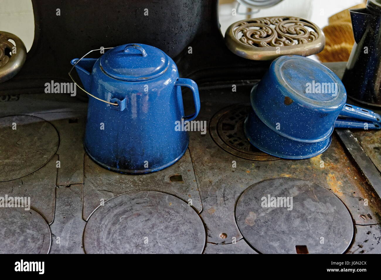 Blue pots on an antique wood burning cook stove - Stock Image