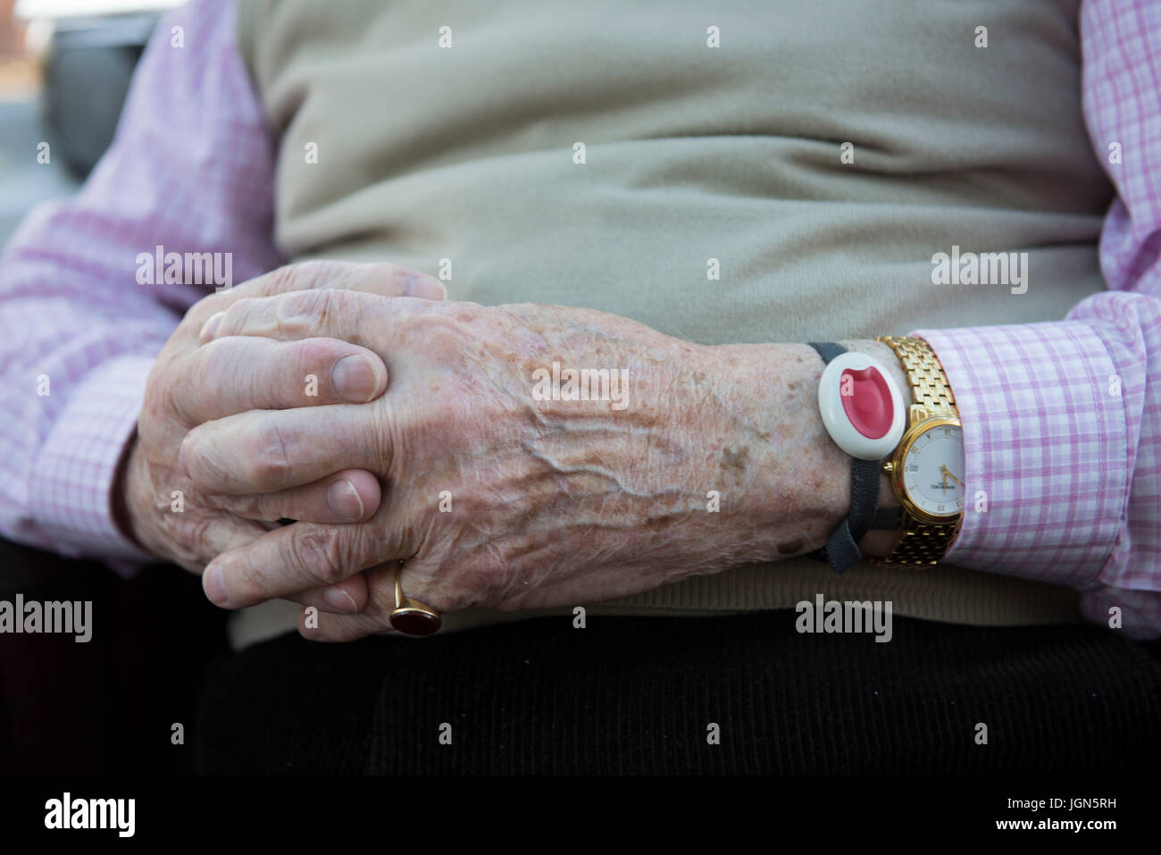 A vulnerable old age pensioner wears a panic alarm wristband. - Stock Image