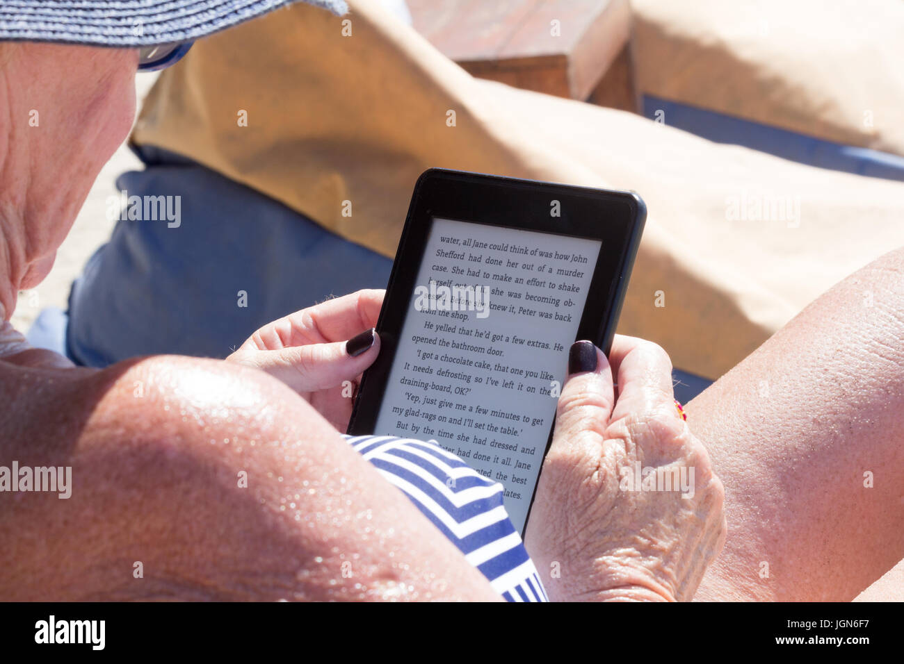Senior woman reading Kindle ebook on a beach in sunshine - Stock Image
