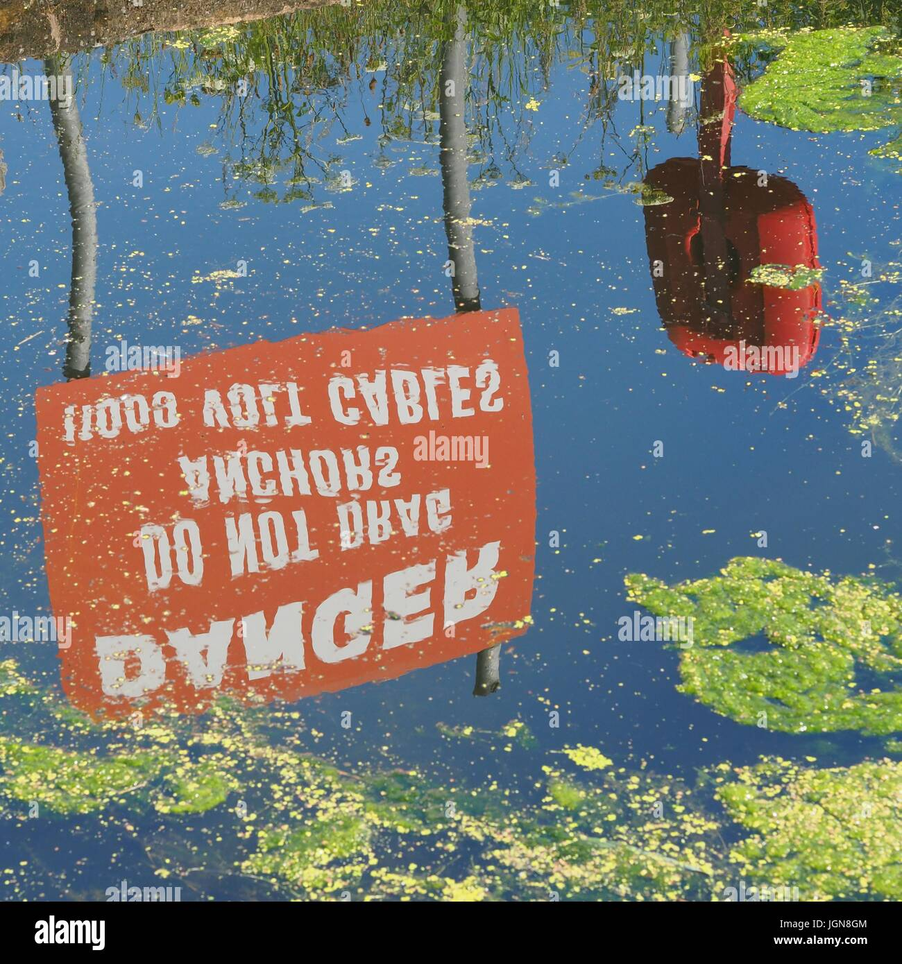 Danger do not drag anchor 11000 volt cable sign and life belt reflected in Exeter Canal Stock Photo
