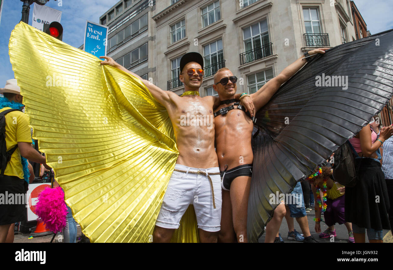 Two guys stretch their black and gold wings at the Pride march in London - Stock Image