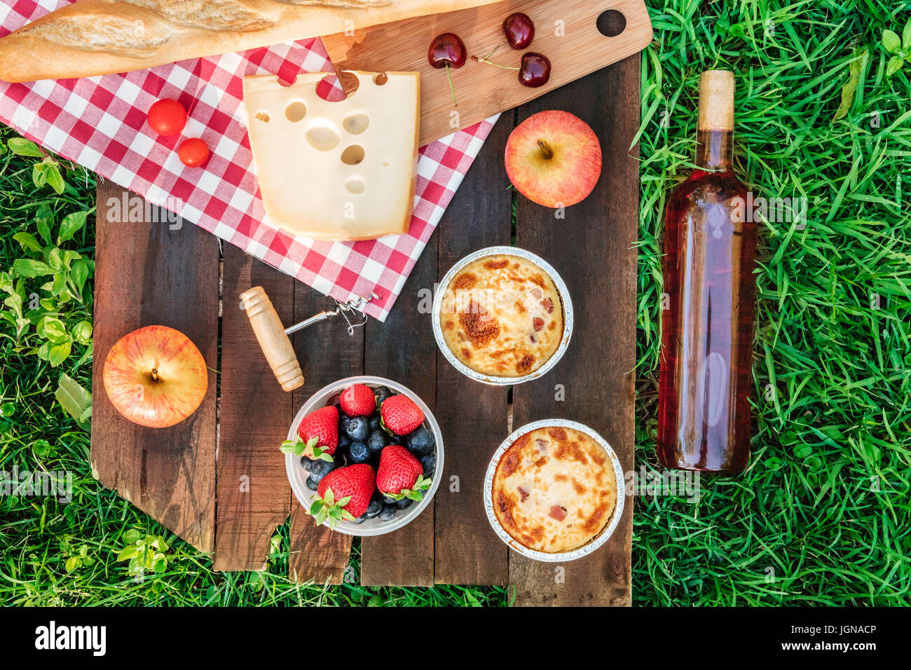 Picnic food and rose wine on wooden board with copyspace - Stock Image