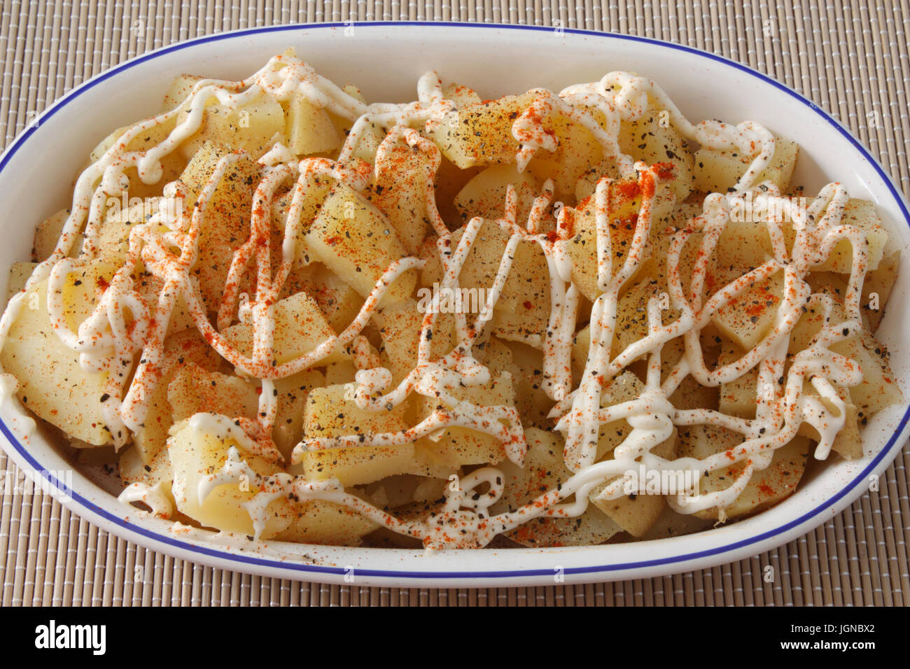 Close-up of potato salad with mayonnaise in oval dish - Stock Image